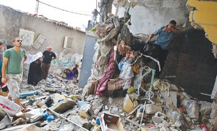 GAZANS EXAMINE the damage from a blast in a house in Deir el-Balah on Monday.