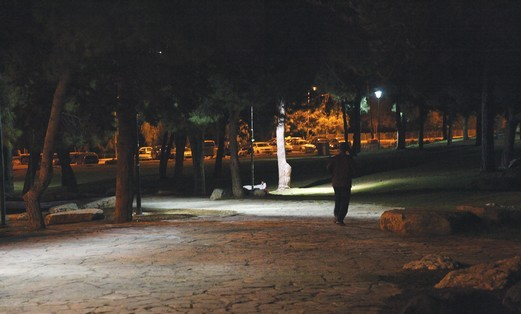 A man jogging through a Jerusalem park at night