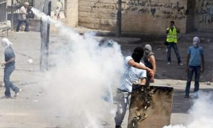 Arab throws back tear gas canister in Silwan