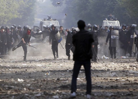 A protester looks on as riot police throw stones during clashes near Tahrir Square (Reuters)