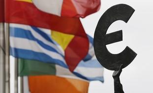Euro symbol near European flags - Photo: REUTERS/Francois Lenoir