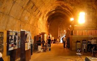 Men pray at the Kotel Tunnels (Photo: BiblePlaces.com)
