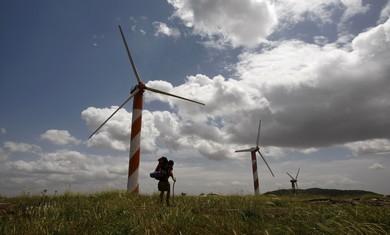 Hiker walks past wind turbines in the Golan Height - Photo: Ronen Zvulun/Reuters