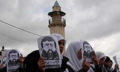 Palestinian students hold signs of Khader Adnan