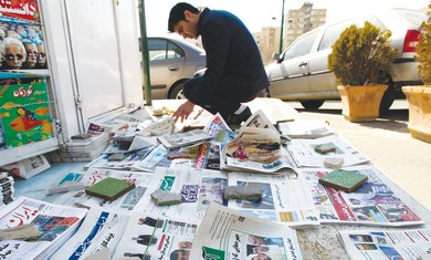 A man looks at a newspaper in Tehran