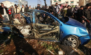 Palestinians look at the remains of exploded vehic