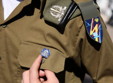 Soldier in Cyber Defenders points to unit's pin - Photo by Marc Israel Sellem