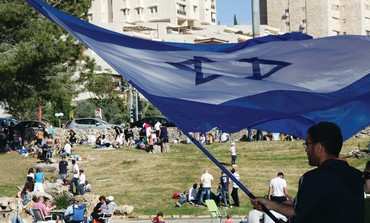 Man waves Israeli flag in Jerusalem