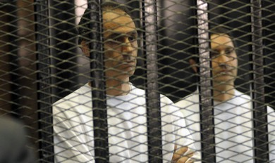 Gamal (L) and Alaa Mubarak, sons of former Egyptian President Hosni Mubarak, stand inside a cage at a courtroom in Cairo (Reuters)