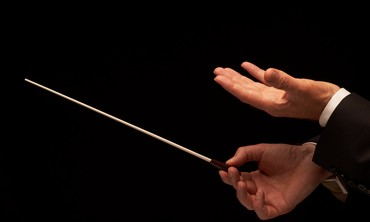 Concert conductor holds baton (illustrative)