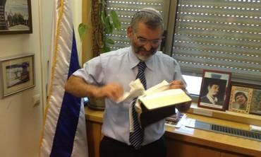 """Ben Ari déchirant un """"nouveau testament"""" à son bureau le 22 juillet 2012"""
