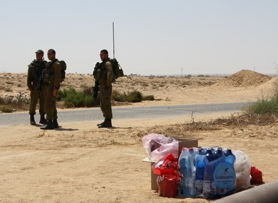 Donated food and water lies near IDF soldiers on Egyptian border (Photo: Ben Hartman)