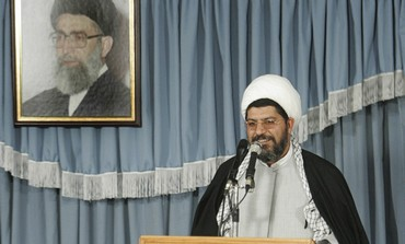 Ali Shirazi speaks under picture of Ayatollah.