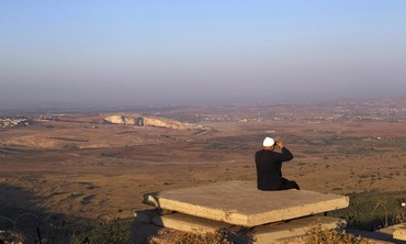 Druse resident looks out at Syria from the Golan -Photo: Ronen Zvulun/Reuters