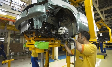 Iranian employees assemble car in Tehran plant