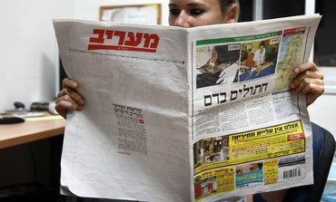 Woman reads Ma'ariv newspaper