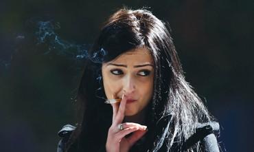 La mujer fuma un cigarrillo