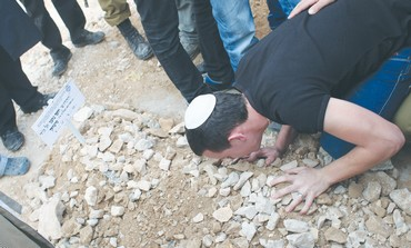 MOURNER kisses the grave of Cpl. Yosef Fartuk