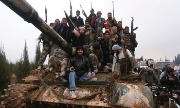 FREE SYRIAN Army fighters pose on a tank