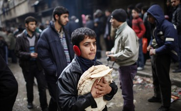 Boy holds bread outside a bakery in Aleppo