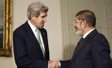 US Secretary of State John Kerry (L) shakes hands with Egypt's President Mohamed Morsi in Cairo