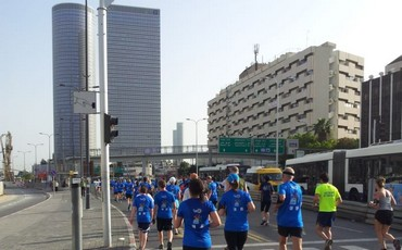 Tel Aviv marathon participants run down Menachem Begin road