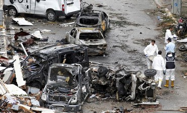 Officials work on one of the scenes of the twin car bomb attacks in the town of Reyhanli.