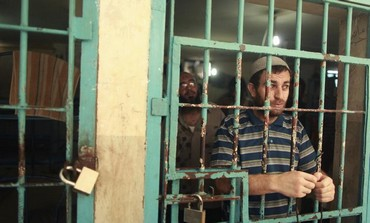 A Palestinian inmate stands behind the bars of a Hamas-run jail in Gaza City, July 23, 2012.