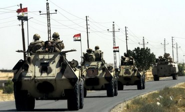 Military vehicles proceed northeast of Cairo May 21, 2013.