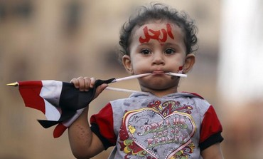 "A girl with the colours of the Egyptian flag and the word ""leave"" painted on her face"