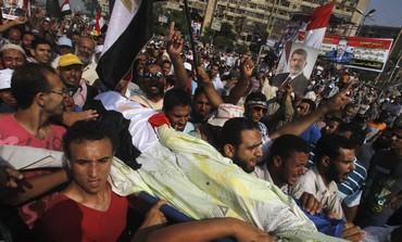 Morsi supporters carry body of man killed by violence outside the Republican Guard headquarters Photo: REUTERS
