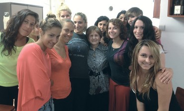 Holocaust survivor Leah Kaufman poses with students after delivering lecture about her past.