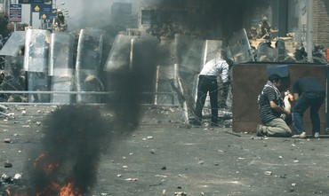 ISLAMISTS TAKE cover as they battle riot police and soldiers in Cairo's Rabaa Adawiya Square, Aug 14