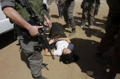 French diplomat Marion Castaing lays on the ground after Israeli soldiers carried her out of her truck (Reuters)