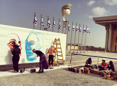 Artists paint graffiti outside the Knesset. (Lahav Harkov)