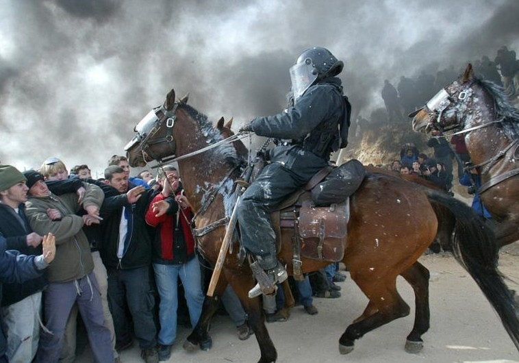 Mounted Israeli police scuffle with pro-settler supporters at the Amona outpost, February 1, 2006. Credit: Reuters