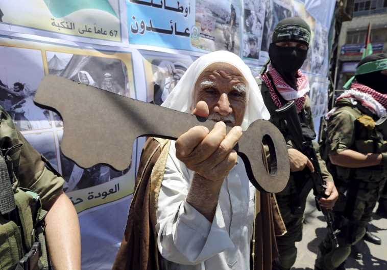 A Palestinian man holds a symbolic key next to Hamas militants during a rally after Nakba Day in Rafah, 2016 (REUTERS)