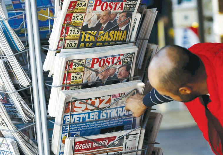 A MAN looks at newspapers at a kiosk in Diyarbakir in November 2015. (Reuters)