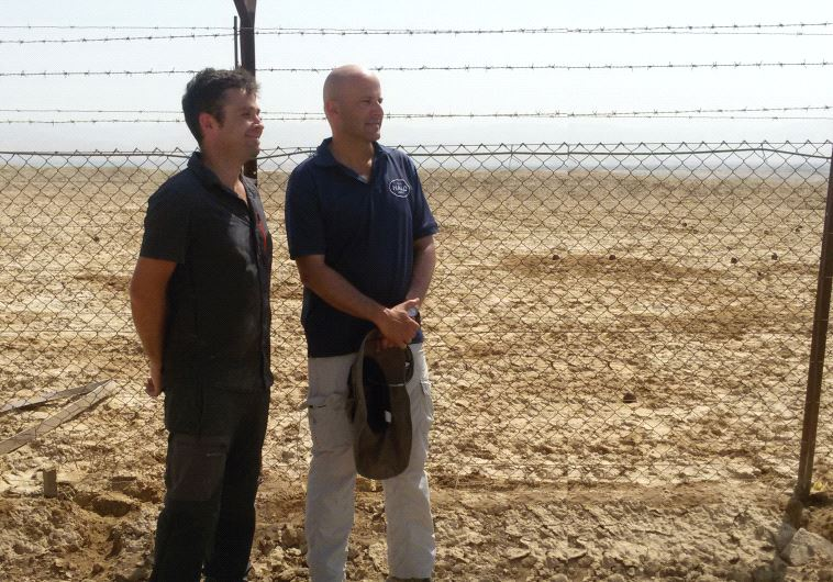 Michael Heinman (left) and Ronen Shimon stand behind a fence marking off mines at Qasr el-Yahud (photo credit: JUDITH SUDILOVSKY)