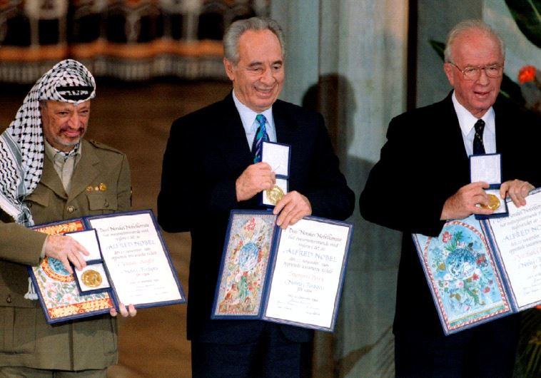Former PLO chairman Yasser Arafat, then foreign minister Shimon Peres and then prime minister Yitzhak Rabin (from L to R) show their shared Nobel Peace Prize awards to the audience in Oslo on December 10, 1994 (photo credit: REUTERS)