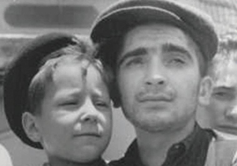 Sailing home: Lulek is held by a fellow Buchenwald survivor, Elazar Schiff, as they arrive in Haifa aboard the 'RMS Mataroa' on July 15, 1945 (photo credit: Courtesy)