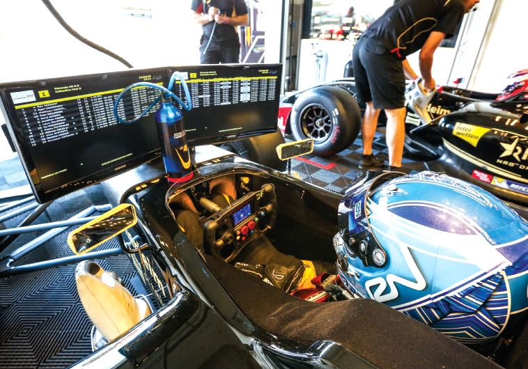 Nissany reads a board attached to his car that relays information about the race (photo credit: Courtesy)