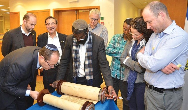 JERUSALEM MAYOR Nir Barkat inspects the Torah scroll donated in memory of Shira Banki to a synagogue in the Katamonim neighborhood. (Jerusalem Municipality)