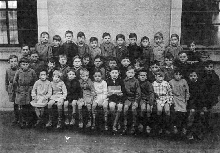 Ehud Loeb (center, holding a sign) at a school in France during the war (Yad Vashem)
