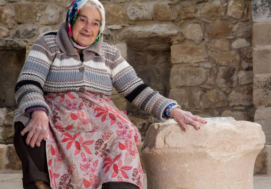 Margalit Zinati, of the Peqi'in village, poses with the ancient stone. (Courtesy of Beit Zinati)