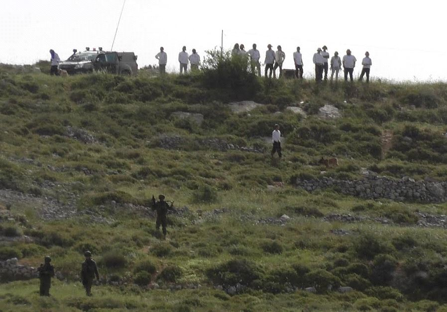 Settlers and IDF soldiers stand on a hilltop outside the Yitzhar settlement