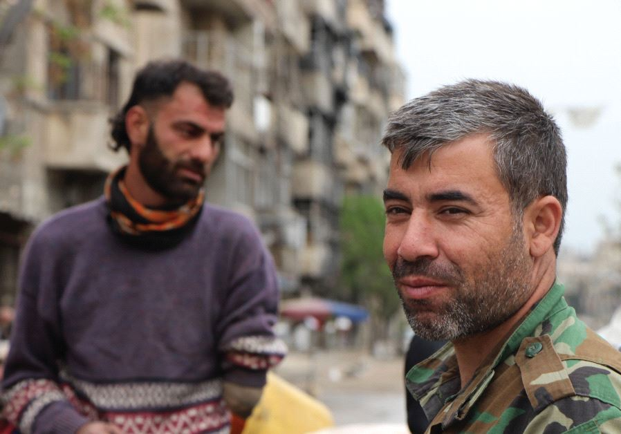 A volunteer with the Iranian-trained National Defense Forces is seen with a disabled veteran of the Syrian Army in the Bustan al-Qasr neighborhood of Aleppo (Jonathan Spyer)