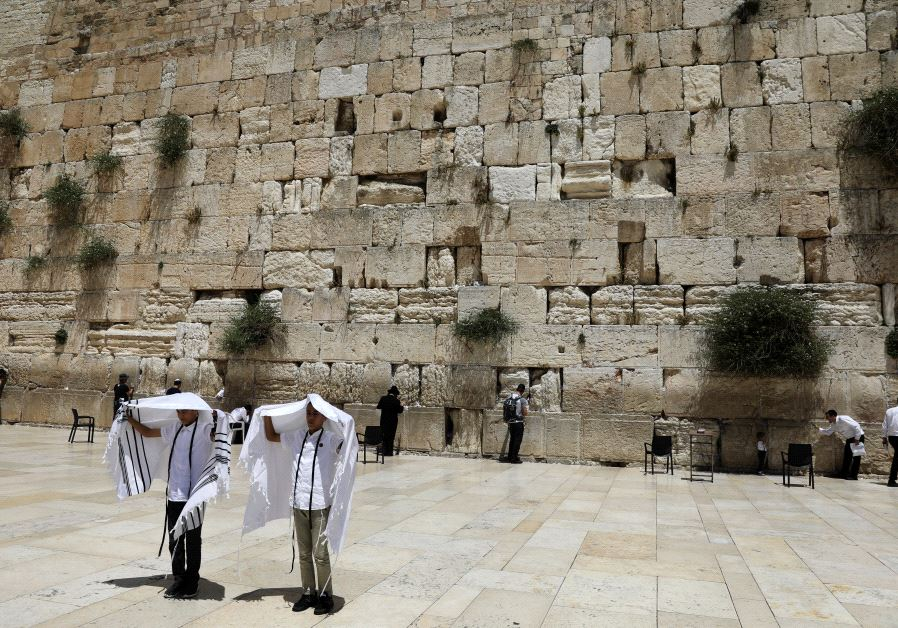 Youth hold their prayer shawls as they stand in front of the Western Wall, Judaism's holiest prayers site in Jerusalem's Old City May 17, 2017. (REUTERS/Ronen Zvulun)