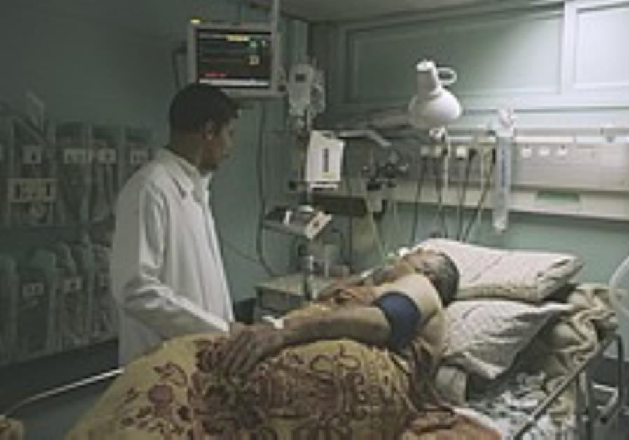 A Palestinian doctor tends to a patient at Shifa H