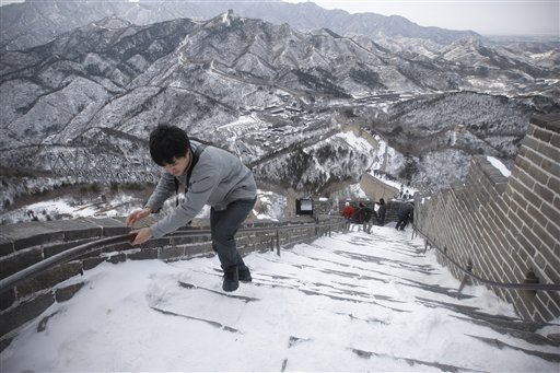 Tourists walk in snow on the Great Wall of China,